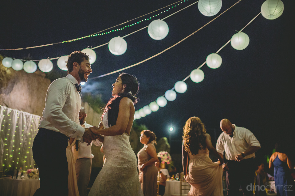 newlywed couple dance at night under green lights surrounded by