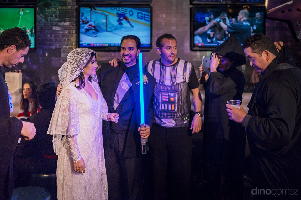 groom holds blue lightsaber and bride at wedding reception at ro