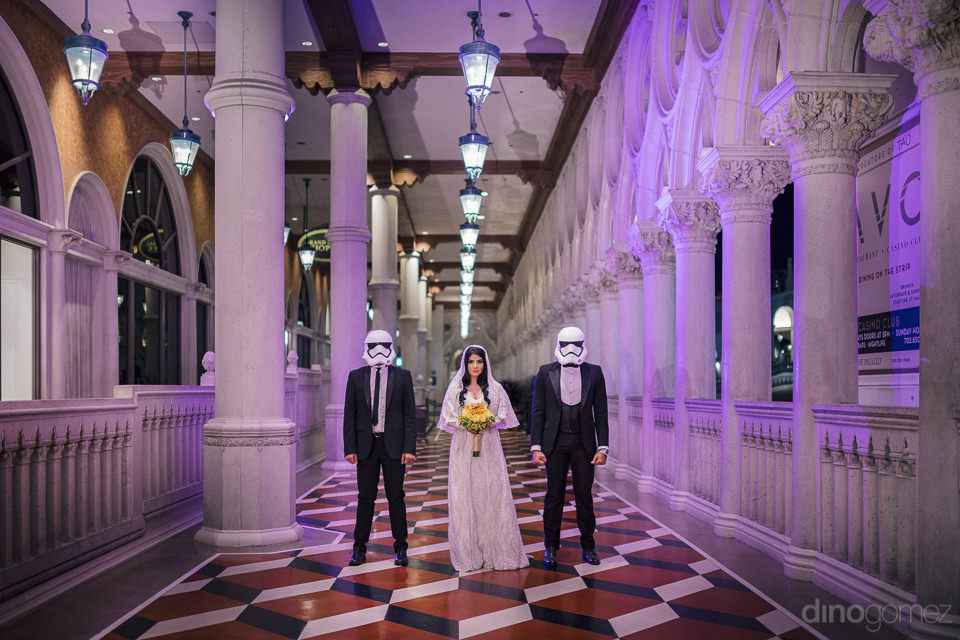 bride standing between two storm troopers in long hallway inside