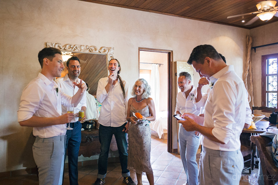 groom and groomsmen laugh in their hotel room before the wedding