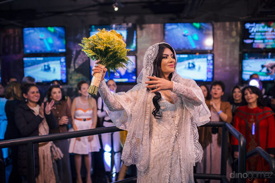bride lifts up yellow rose bouquet before tossing it to the fema