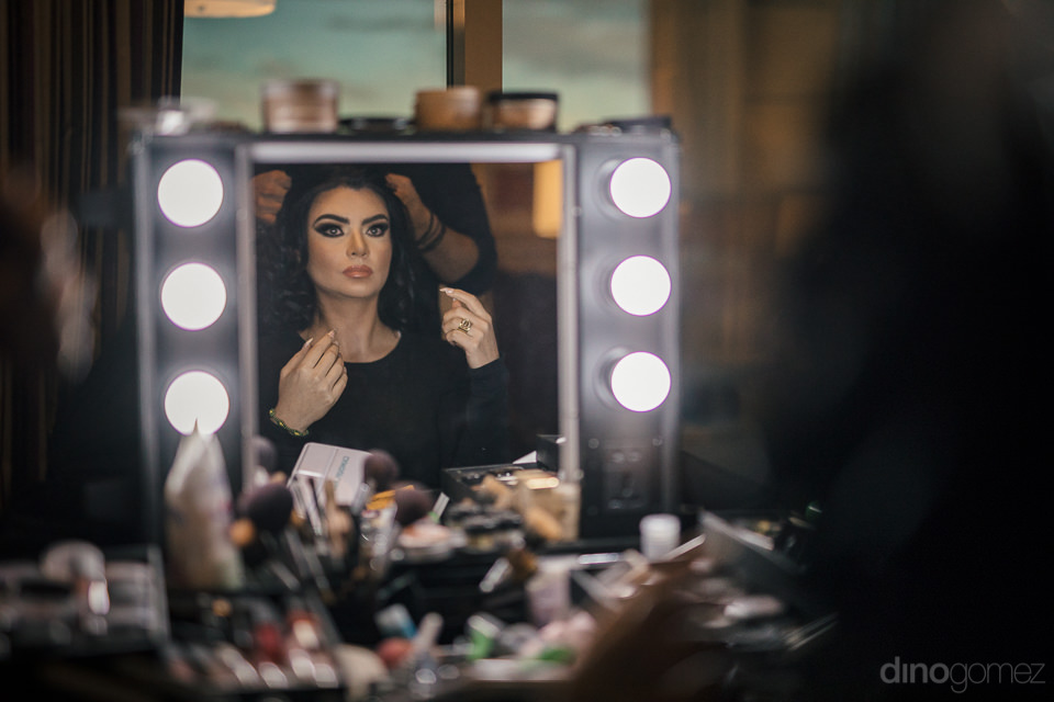 beautiful bride looks into mirror while getting her make up done