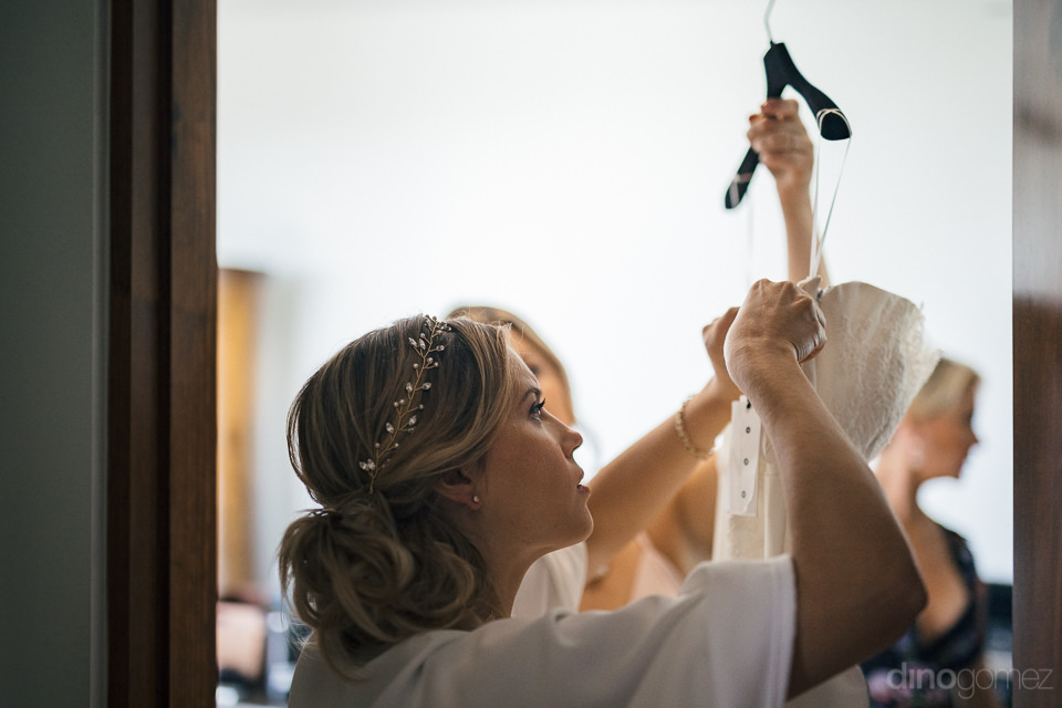 bride holds up wedding dress on hanger while bride inspects it b