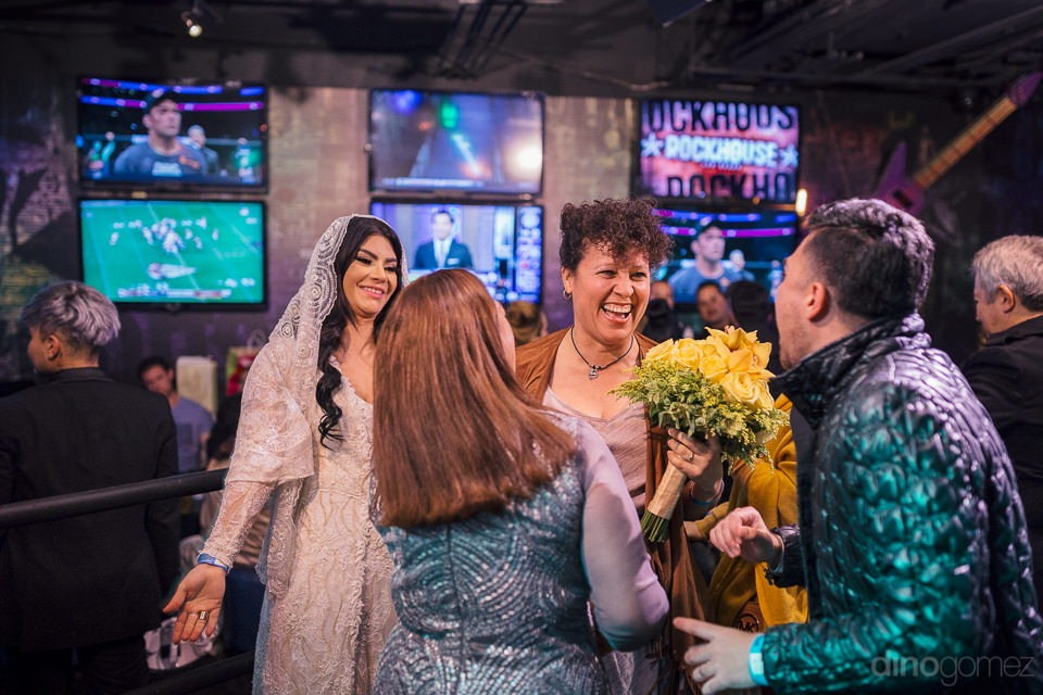 brides friend catches bouquet and is congratulated by other wedd