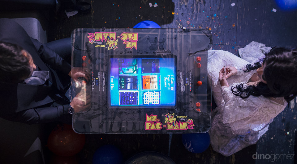 bride and groom play retro ms pac-man arcade game in overhead ph