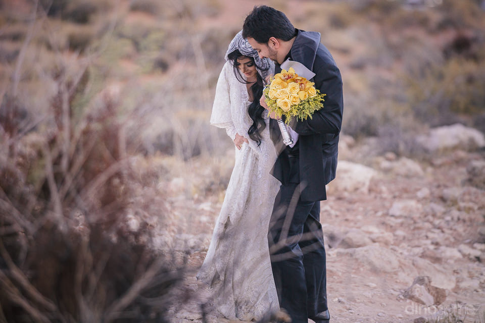bride and groom walk through rough desert terrain in wedding pho