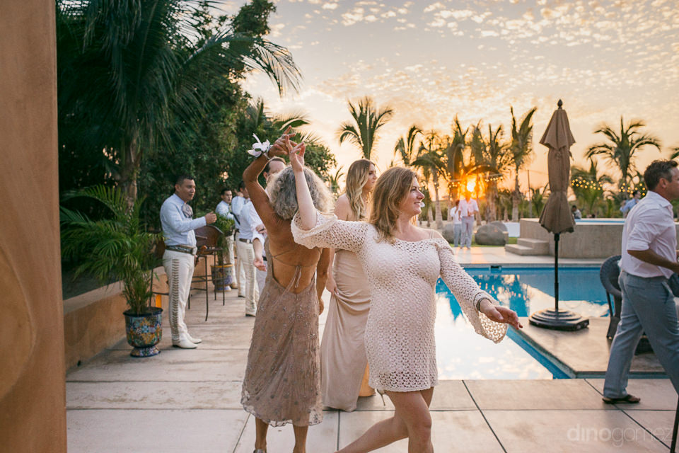 wedding guests arrive to reception by the pool at sunset at ranc