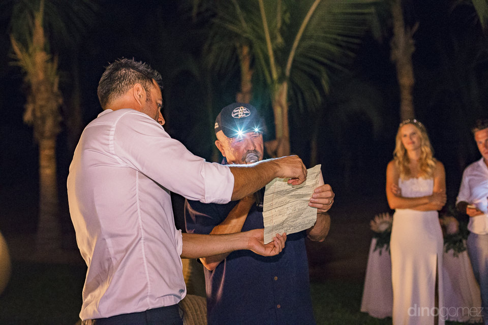 groom helps father of the bride hold the paper with his wedding