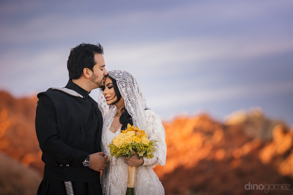 groom kisses forehead of bride as they stand on red desert mount