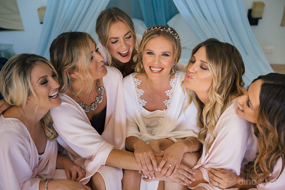 bride and bridesmaids huddle together for photo before the weddi