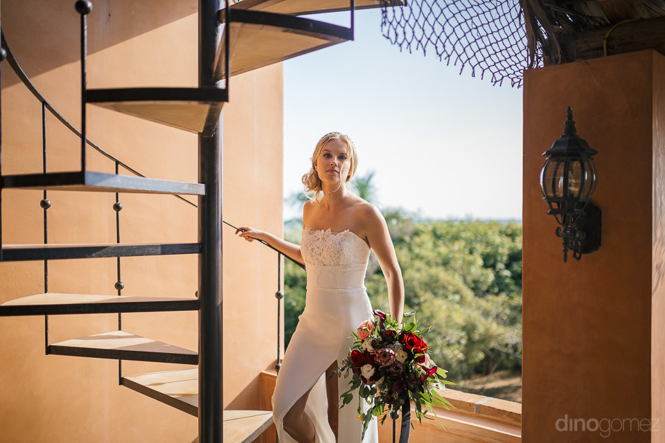 beautiful blonde bride in wedding dress stands in hallway under