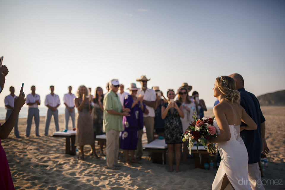father walks bride down the aisle on the beach at wedding ceremo