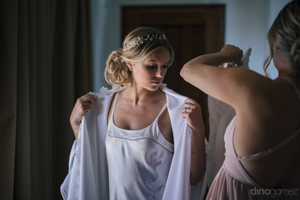 bride begins to take off her white satin robe and put on her wed