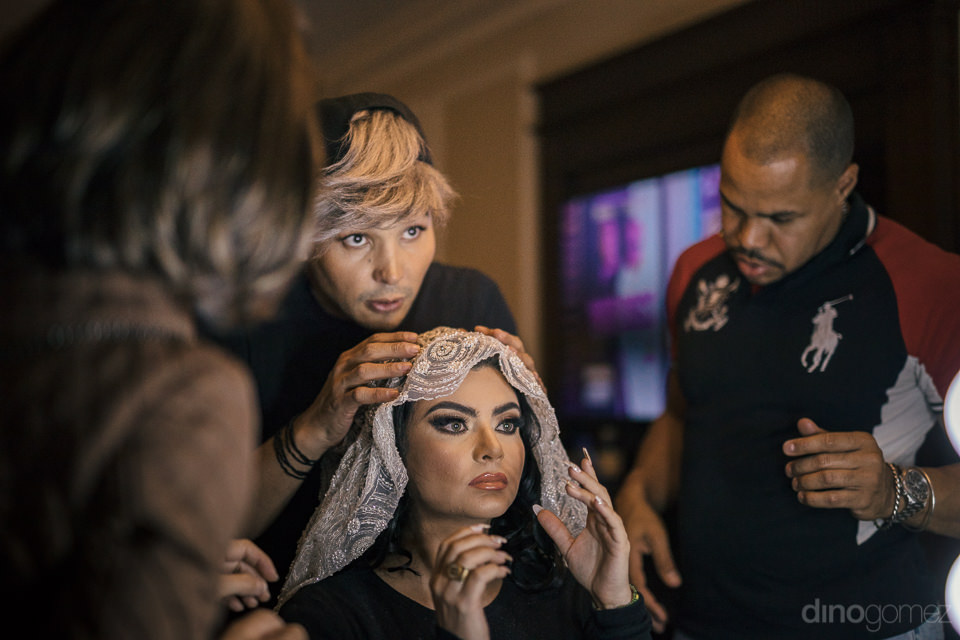 makeup artists gently place the brides veil on her head to compl