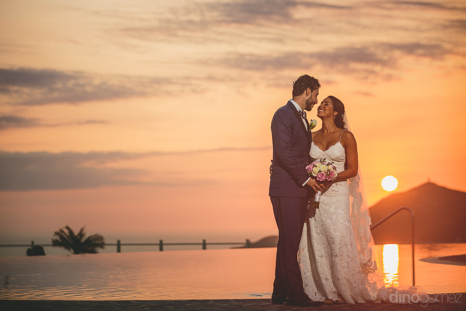perfect mexico destination wedding sunset newlyweds in front of
