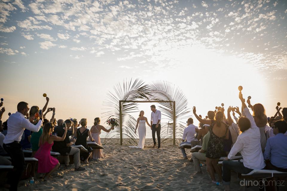 wedding guests raise and shake maracas to celebrate newlyweds ju