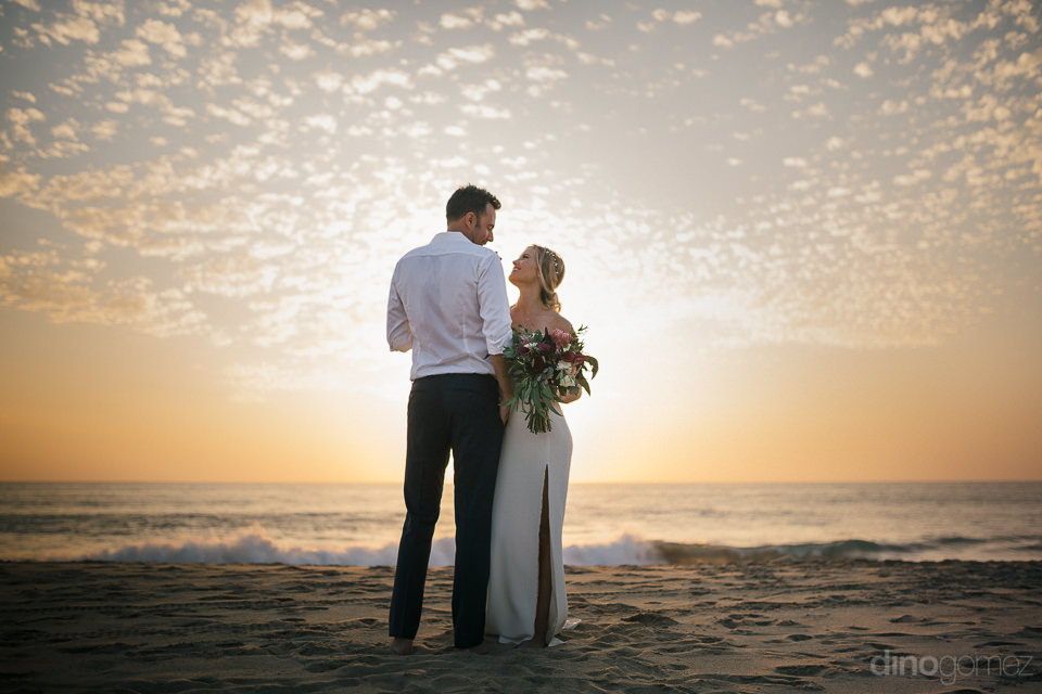 perfect wedding photo of newlyweds on beach with their bodies bl