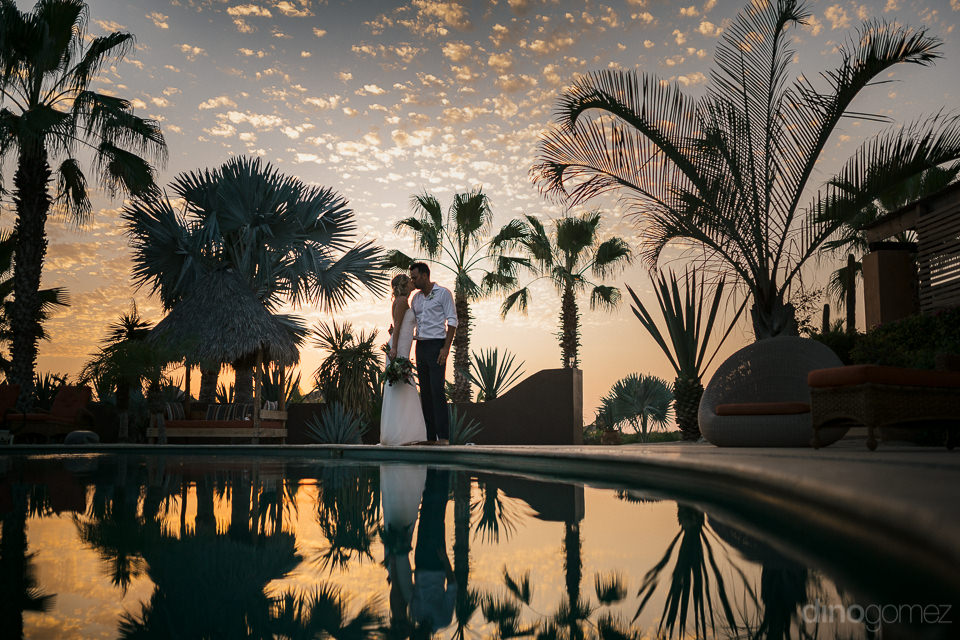 sunset wedding photo with newlyweds standing by the pool with th