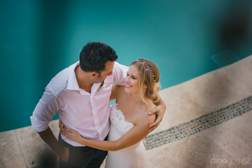 photo from above of the bride and groom hugging by the pool