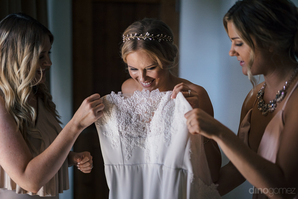 two bridesmaids help the bride into her wedding dress on her wed