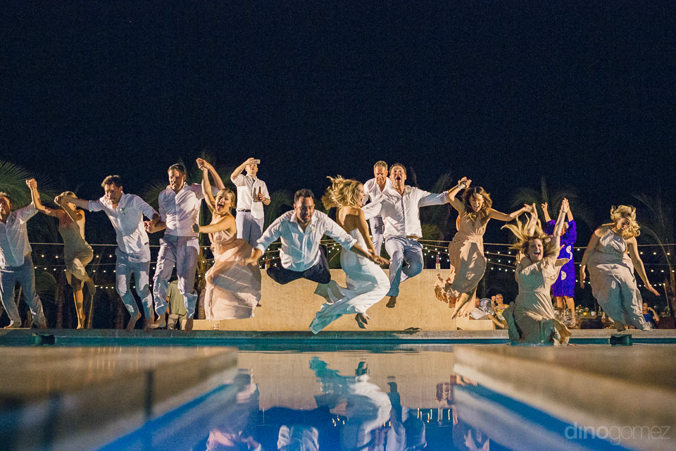 wedding party all jump into pool together at wedding reception