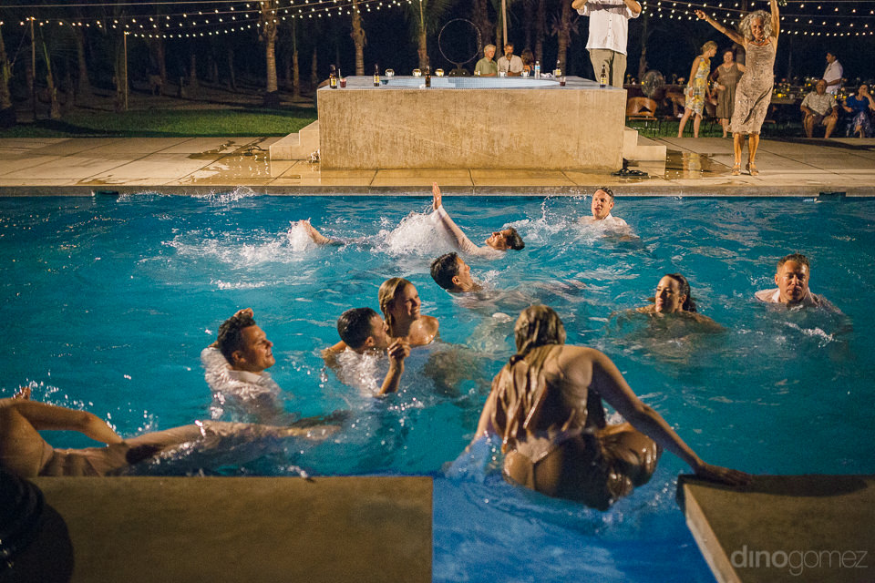 newlyweds and guests jump and swim in pool in the middle of the