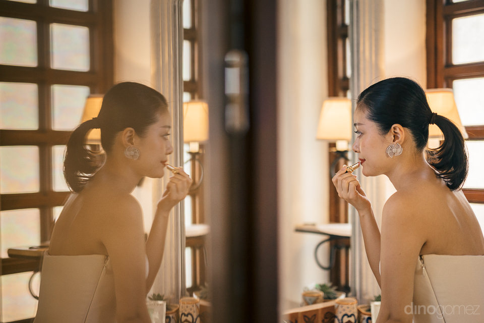 bride looks in mirror puts on lipstick refection inside las vent