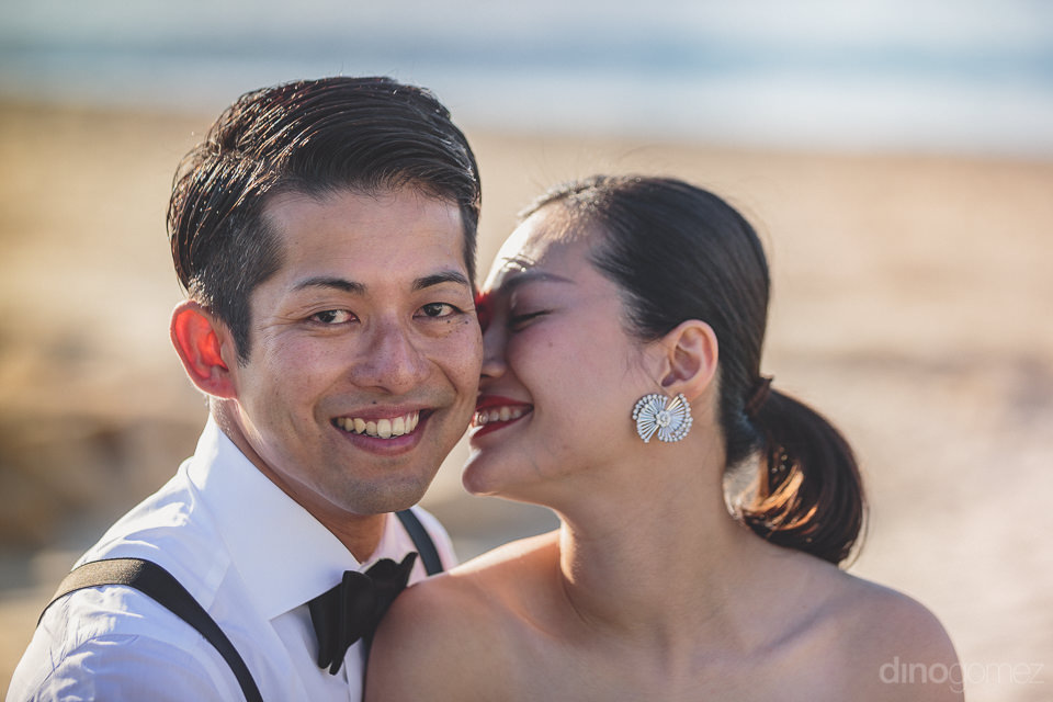 heartwarming photo of young newlyweds together on cabo beach by