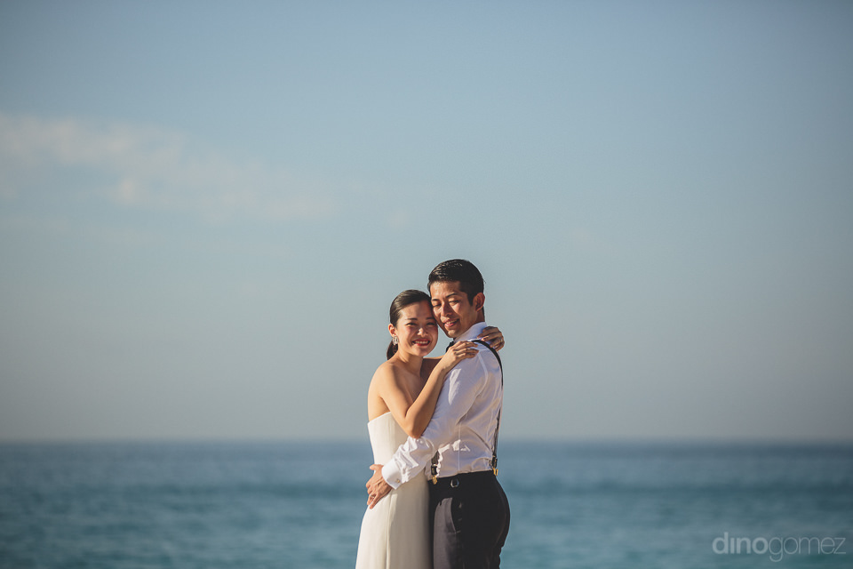 newlyweds hug in front of blue sky and ocean view from las venta
