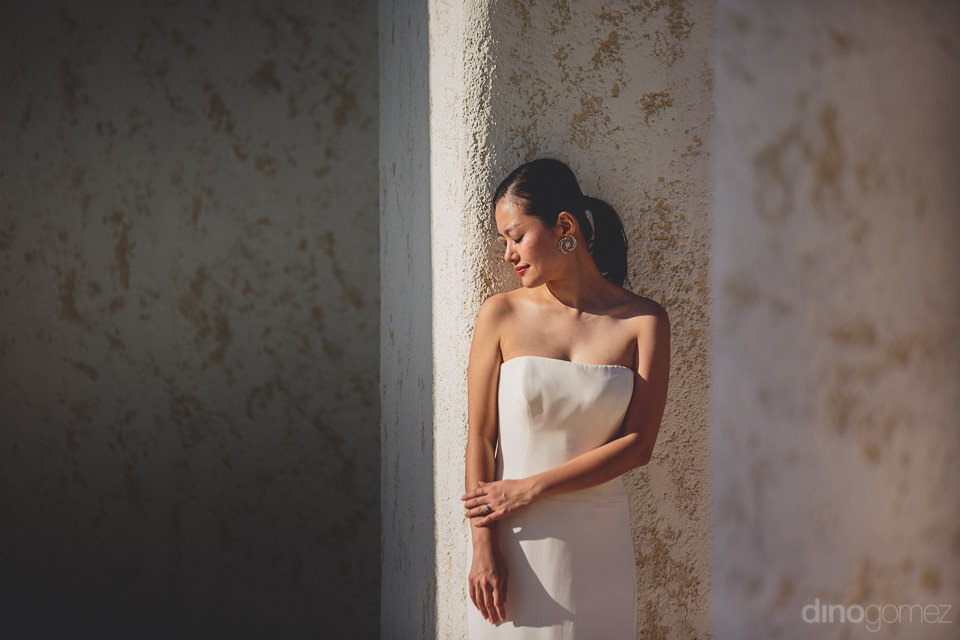 beautiful bride in sleeveless white dress stands against white w