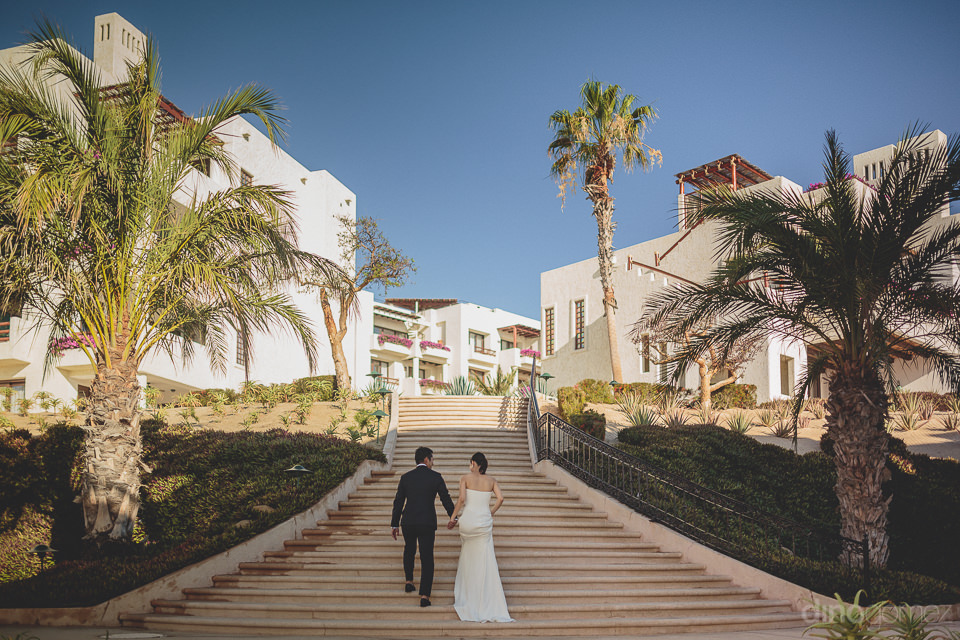 newlyweds hold hands and walk up long staircase in mexican villa