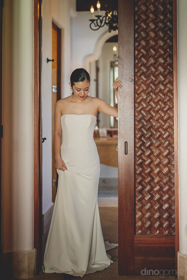 bride from japan poses in doorway of mexican villa in photo by i
