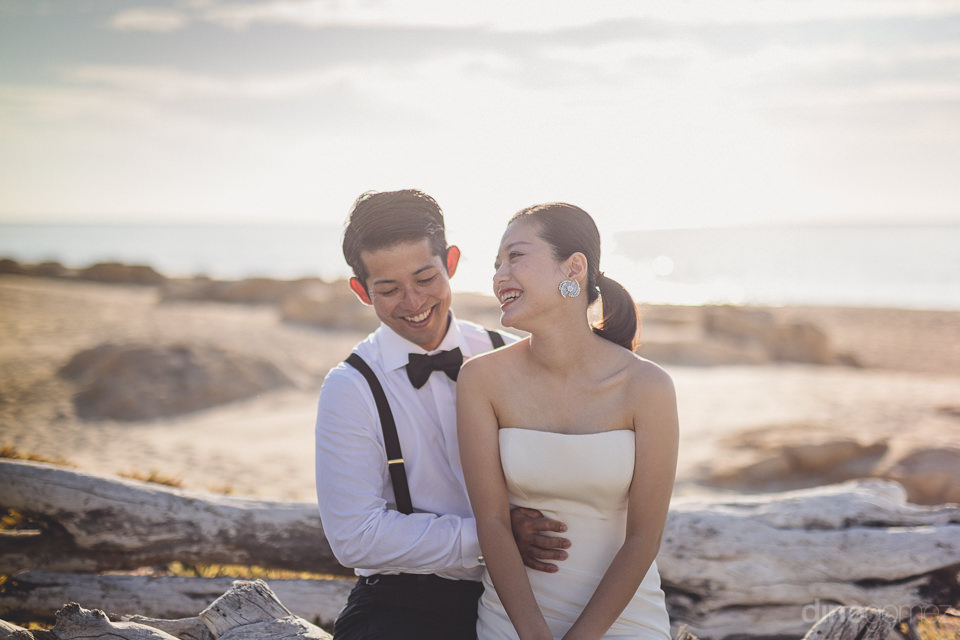 newlyweds sit together on beach drift wood in cabo mexico weddin