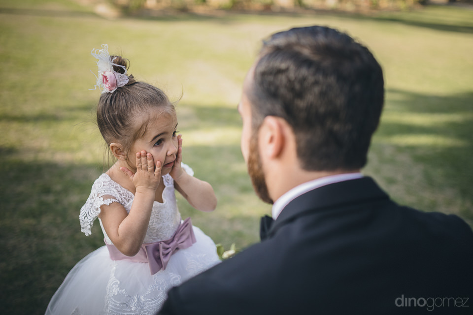 cute little flower girl in white dress and purple bow tie belt