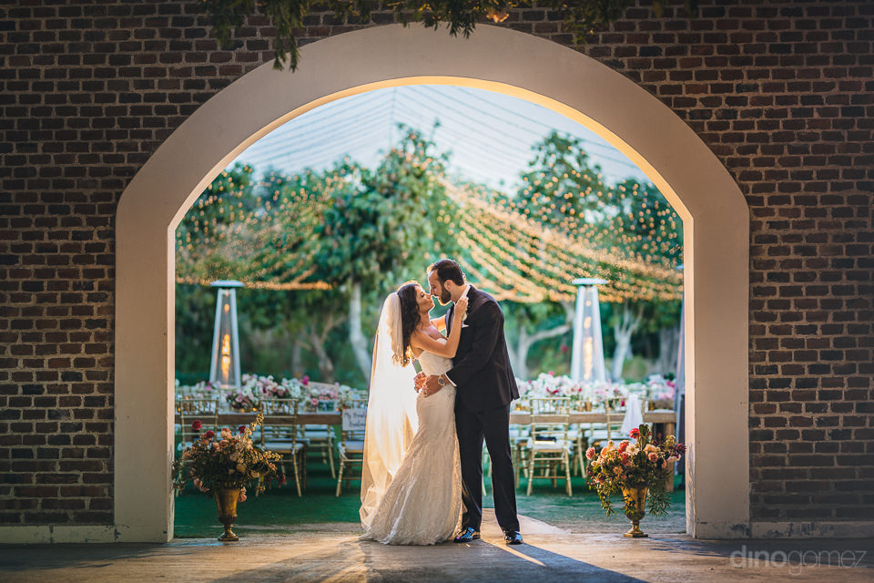 newlyweds stand in archway of brick barn at flora farms at weddi