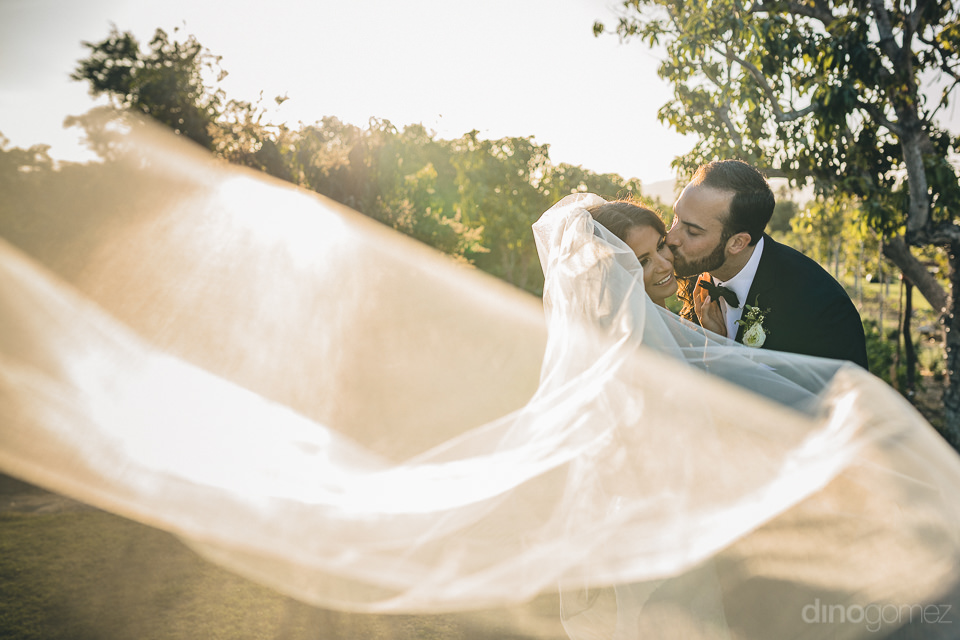 newlyweds kiss white wedding veil flows floats through air artis