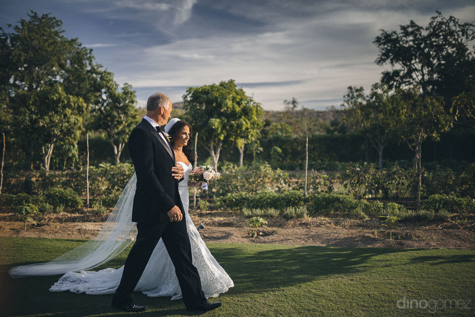 father walks with bride daughter through garden towards altar at