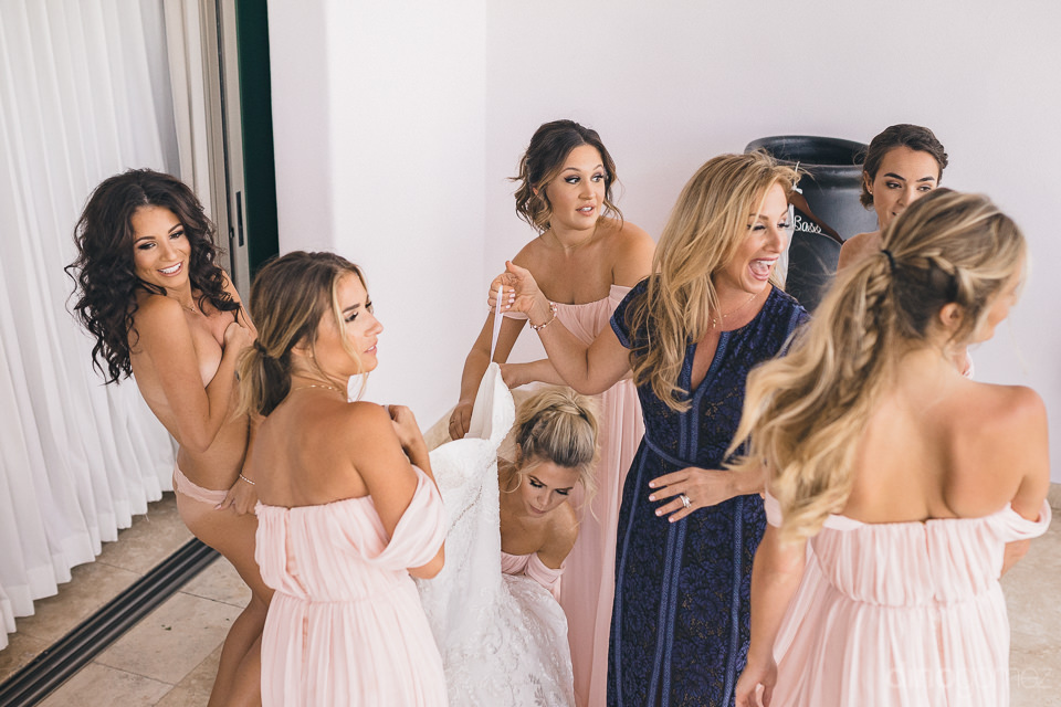 bride getting into wedding dress with help of bridesmaids before