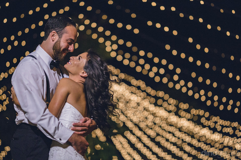 event tent lights look like stars as newlyweds hug under the nig