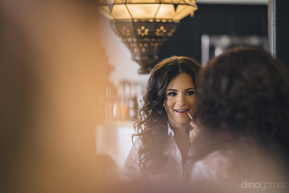 bride puts on lipstick in the mirror before the wedding in photo