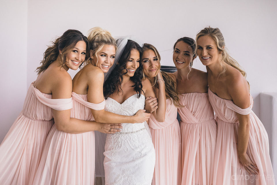 five bridesmaids in pink dresses with bride in white dress toget