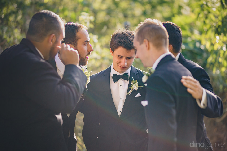 groom talks to groomsmen before wedding ceremony begins at luxur