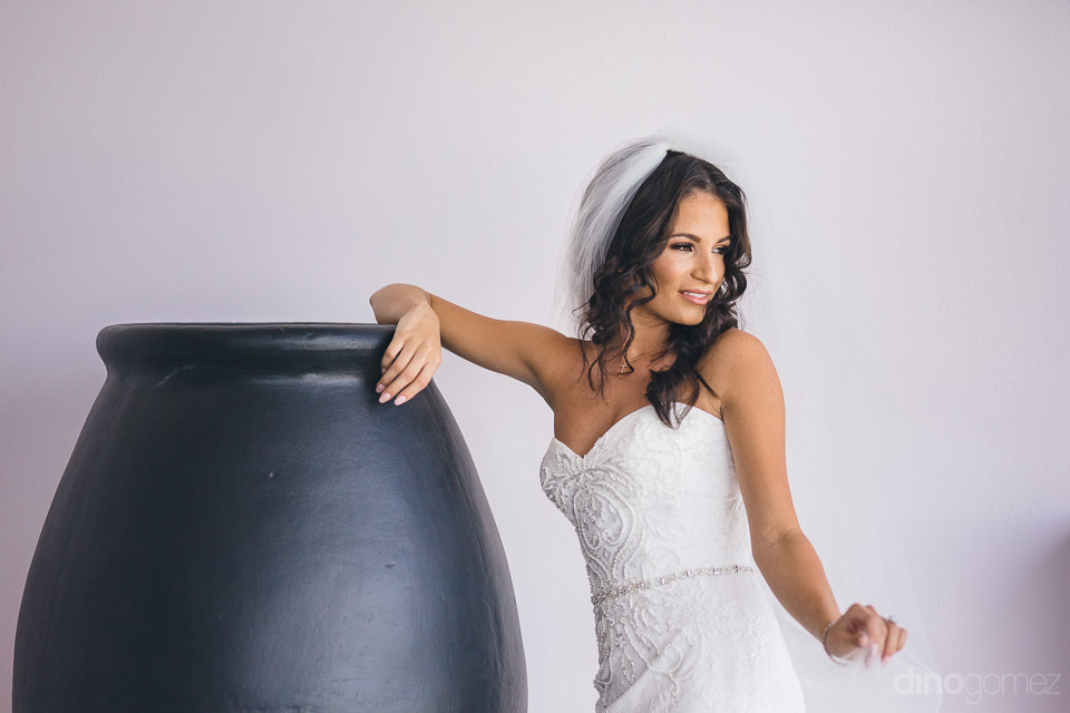 pretty bride in wedding dress leans on black ceramic barrel in c