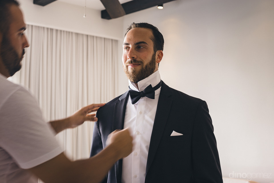 groom in classy black suit and bow-tie for high-end wedding in c