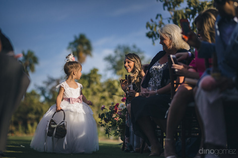 flower girl throws flowers as guests smile and laugh at outdoor