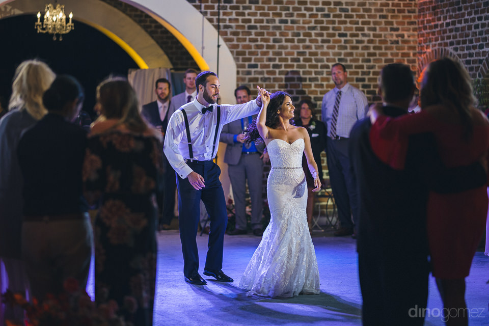 newlyweds dancing under blue lights as wedding guests watch them