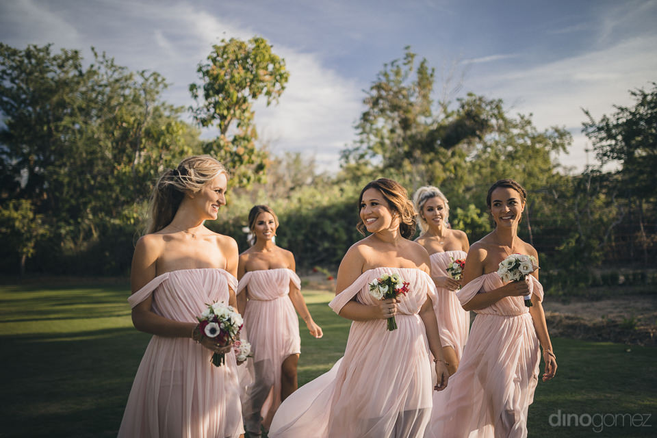 fairy tale bridesmaids in pink dresses walk through beautiful ga