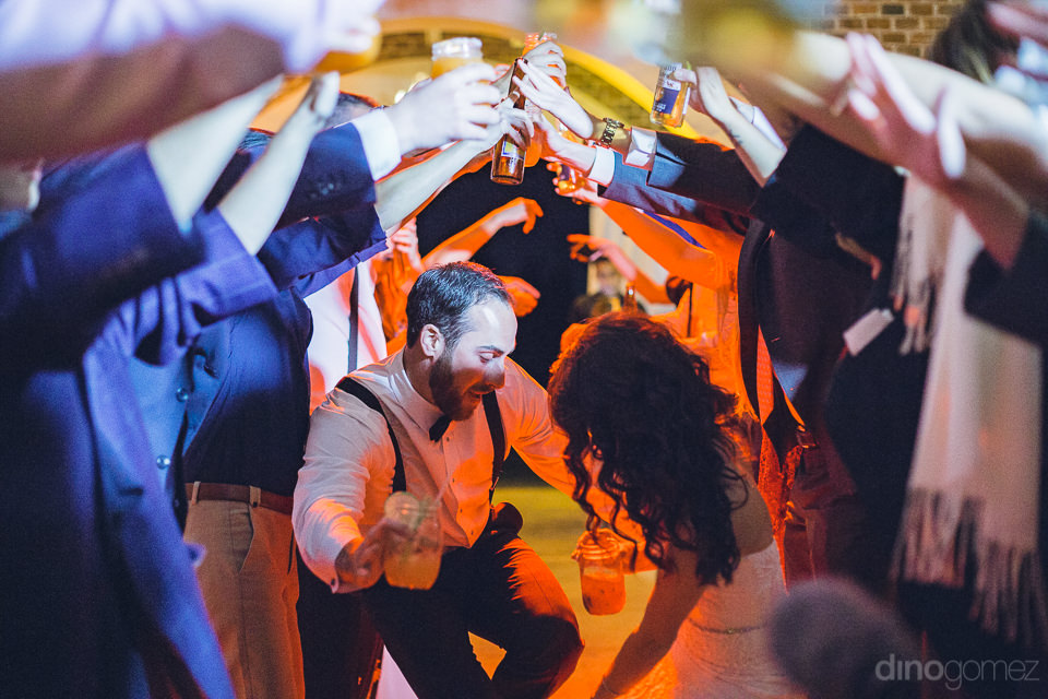 newlyweds dance low while guests gather round and hold up their