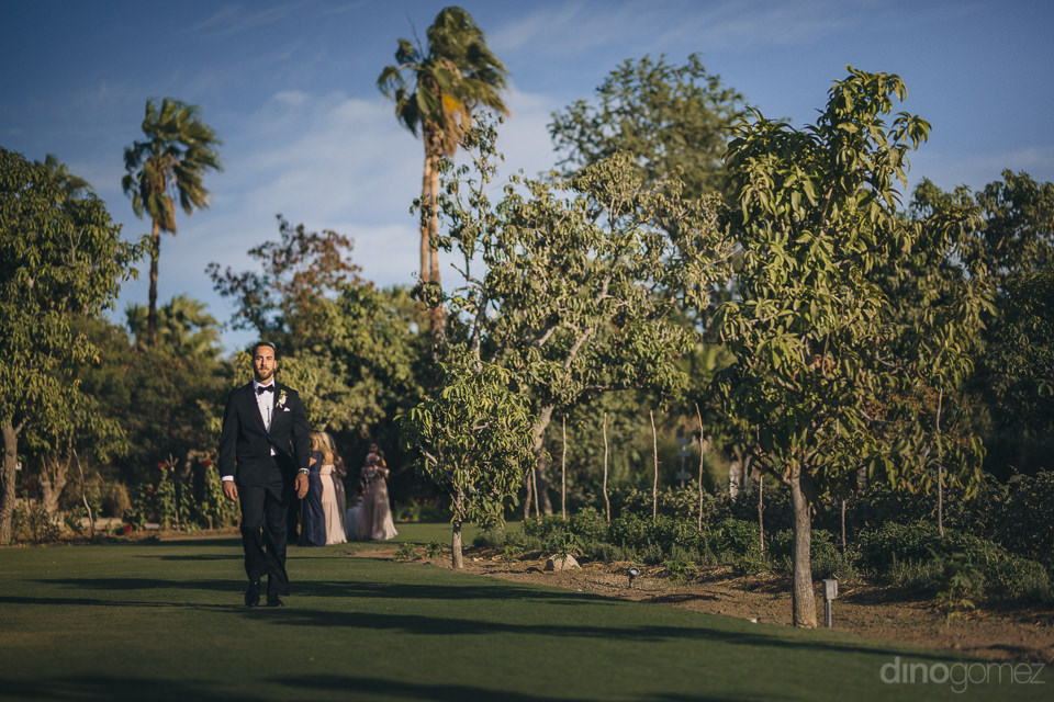 groom walks by himself through the lush green gardens of flora f