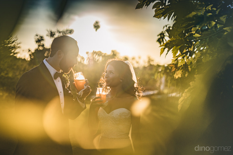 newlyweds drink tropical drink in artistic wedding photo by cabo